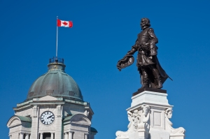 Monument to Samuel De Champlain, founder of the Quebec City with the old Post Office tower in the back, Place D'Armes, Quebec City, Canada. Credit: © Shutterstock.